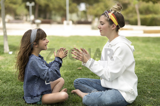 Two sisters playing in a park sitting on the grass.