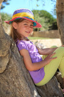 Girl sitting on an olive tree trunk