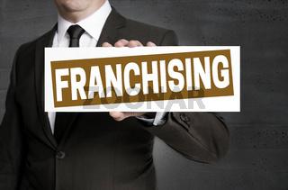 Franchising Schild wird von Geschäftsmann gehalten