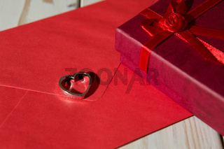 Closeup of a silver heart pendant on a red envelope and gift box