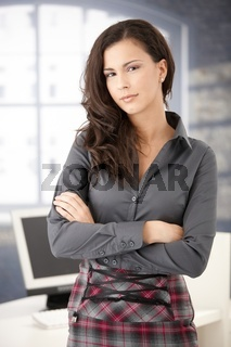 Pretty office worker standing in office smiling