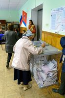 An older woman puts the ballot in the ballot box at polling stations on the day of elections to the State Duma