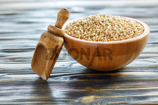 Green buckwheat in bowl and wooden scoop.
