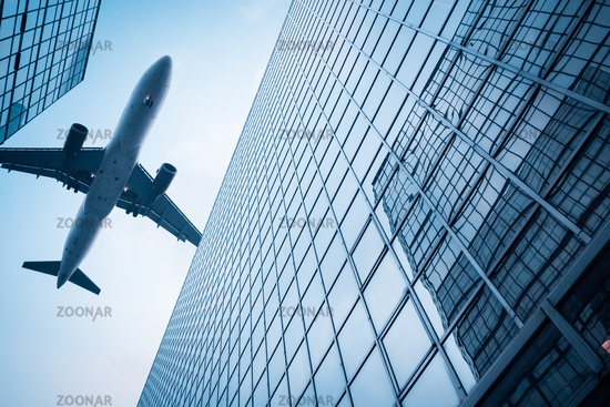 airplane above modern building