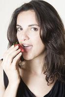 Frau isst eine rote Erdbeere