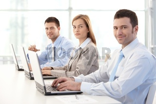 Young businesspeople working on laptop smiling