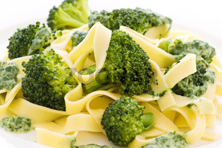 Tagliatelle with broccoli and pesto sauce as closeup on a white plate