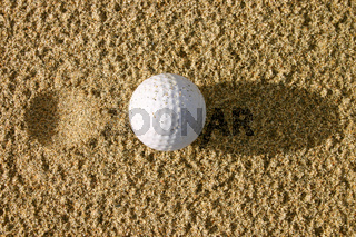 Golf ball in the sand with a pitch mark