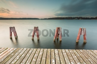 Beautiful lake landscape with jetty. Long time exposure photo with filter. Polish lake shore at cloudy weather sunset. Dramatic sky scene at sunset.