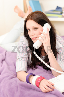 Young student girl speaking on phone lying