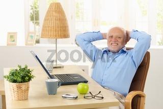 Happy elderly man smiling at desk