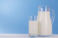 Milch Krug und Glas auf hell blau Hintergrund.