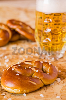 Closeup of salty cooked pretzel and lager beer