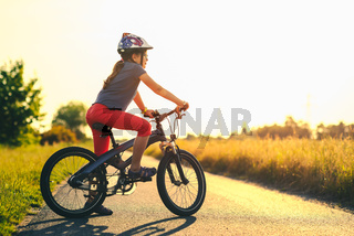 young girl on a mountain bicycle at sunset