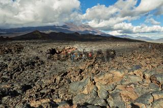 Tourists hiking on lava field eruption Tolbachik Volcano on Kamchatka Peninsula, Klyuchevskaya Group of Volcanoes.