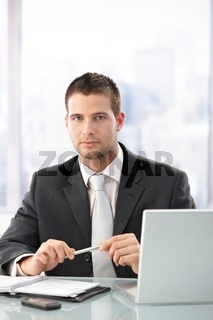 Young executive sitting in bright office