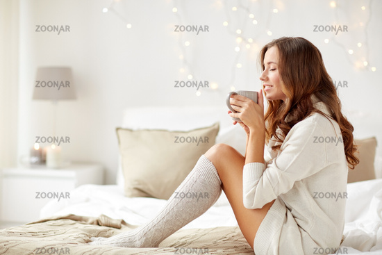 happy woman with cup of coffee in bed at home
