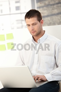 Casual office worker using laptop