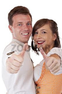 Glücklicher Mann und Frau im Dirndl halten Daumen nach oben. Freigestellt auf weissem Hintergrund.