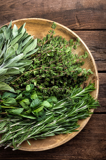 various fresh herbs, rosemary, thyme, mint and sage on wooden background