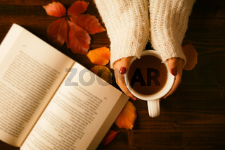 Woman hands holding teacup and opened book seen from above