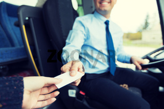close up of bus driver selling ticket to passenger