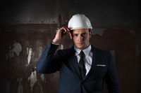 Portrait of a architect in industrial concept in white helmet on dark background
