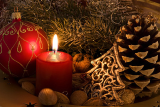 Christmas decoration with candlelight and bauble as closeup