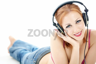Playful girl lies on a white background in the ear-phones