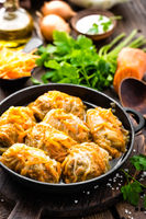 Cabbage rolls stewed with meat and vegetables in pan on dark wooden background