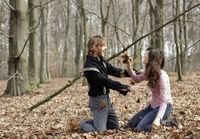 junges Paar wirft Blaetter im Wald