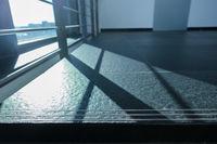 Geländer als Schatten im Gegenlicht auf Fliesen auf dem Boden