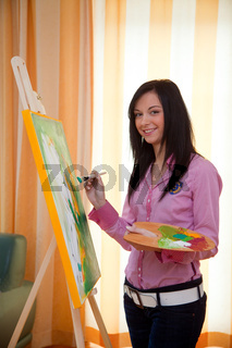 Young woman doing oil painting