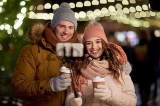 couple with coffee taking selfie at christmas