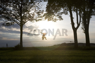 junger Mann auf der Slackline im Sonnenuntergang