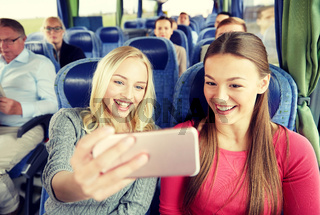 women taking selfie by smartphone in travel bus