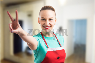 Happy smiling housewife showing peace vistory gesture