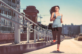 City workout. Beautiful young woman running in an urban setting