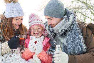 Glückliche Familie trinkt Tee zum aufwärmen