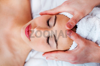 Young pretty girl getting face massage in spa