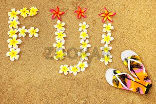 Word Fiji written on a beach with plumeria flowers