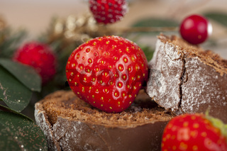 Close up of a sliced christmas chocolate log and strawberries