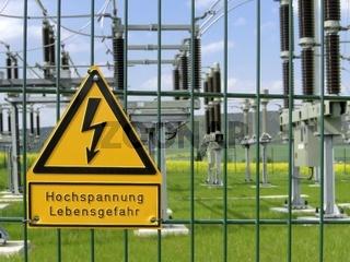 Gelbes Warnschild vor Hochspannung an einem Sicherheitszaun  vor einem Umspannwerk