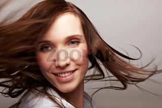 Brünette Frau schüttelt ihre Haare