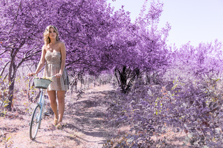 Young woman on bicycle in fantasy pink forest