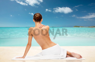 beautiful woman in towel with bare top on beach