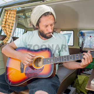 Man Playing Guitar in Camper Van