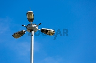 Street lamp on blue sky background photographed at middle of the day.