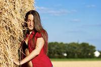 Junge Frau mit verträumten Blick an Stroh
