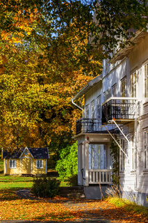Old idyllic wooden house in a park in autumn